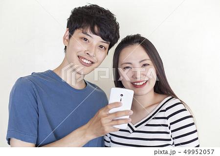05a98d8b4e スマートフォンを使う若い男女. カップル デート スマホ 旅行